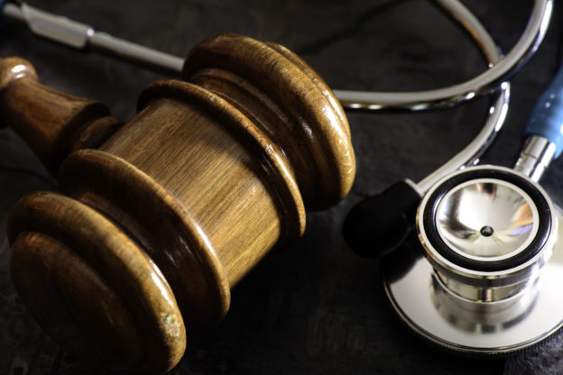 A medical malpractice concept. A close up of a gavel surrounded by a stethoscope.