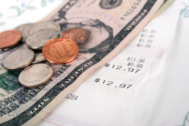 Restaurant bill with dollar bills (tips) on a plate and receipt close up